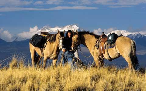 Reiter zwischen zwei Pferden vor Bergpanorama